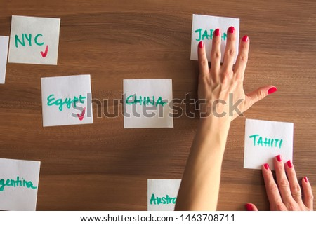 Hands moving travel destinations across a board