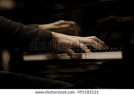 Hands musician playing the piano closeup
