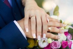 Hands newlyweds on wedding bouquet