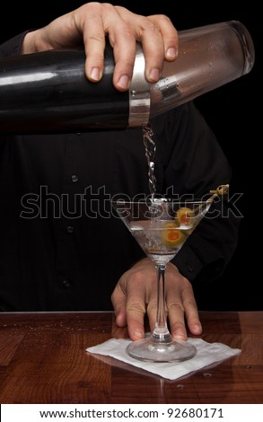 hands of a bartender holding a shaker pouring a drink into a martini glass
