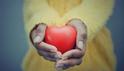Hands of a black woman holding and offering a heart shape. Love, health concept. Selective focus.Cinematic effect.