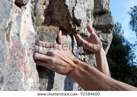 Hands of a boy climbing on limestone, Muzzerone Mountain, Italy