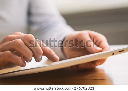 Hands of a business woman hold and use a tablet computer. Shallow DOF, focus on the index finger. #276702821
