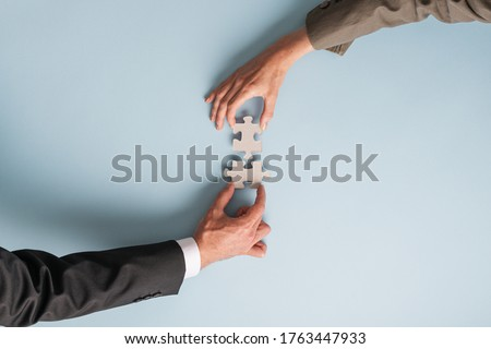 Hands of a businessman and businesswoman joining two puzzle pieces in a conceptual image of merger and partnership.