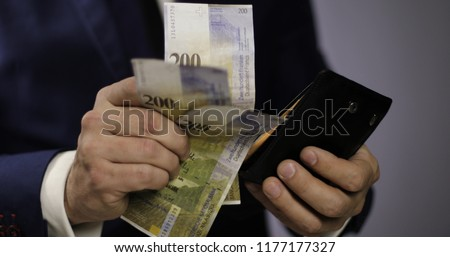 Hands of a businessman get out Swiss francs from their wallet. Swiss currency of 200, 100 francs. Close up.