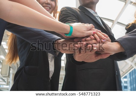 Hands of a businessman holding a stacked show unity to work together. #548771323