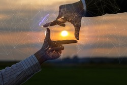 Hands of a businessman show a cropped composition against the backdrop of a sunny sunset.