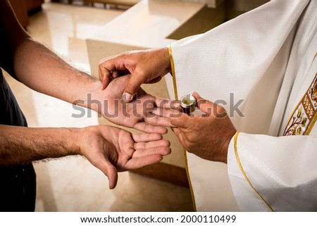Hands of a Catholic Priest applying the oil for the Anointing of the Sick. Sacraments of the Catholic Christian religion in church. ストックフォト ©