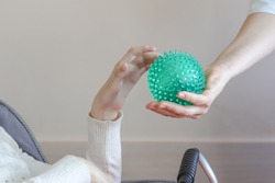 hands of a child with cerebral palsy exercises with a ball development of tactile sensations