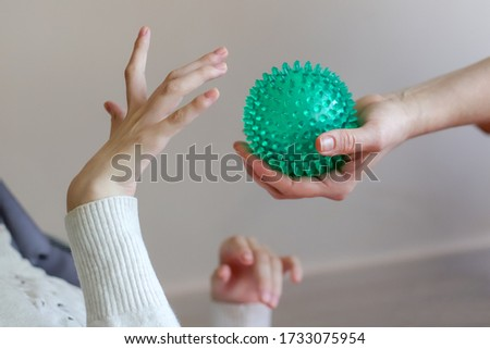 hands of a child with cerebral palsy exercises with a ball development of tactile sensations Stock photo ©