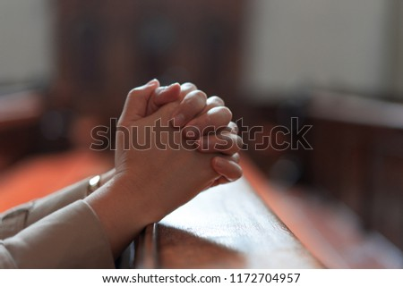 Hands of a Christian girl is sitting and praying with humble heart in the church.