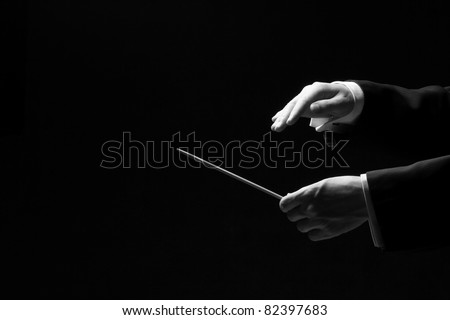 Hands of a conductor isolated on black background, black and white - stock photo