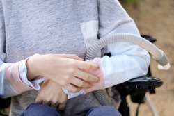 Hands of a disabled person with muscular dystrophy holding a ventilator for deep breathing, concept, background
