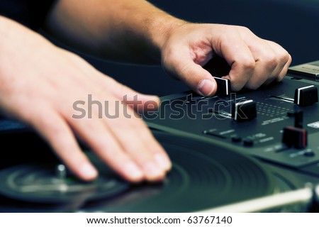 Hands of a disk jockey playing the music on the turntable and top-class mixing controller