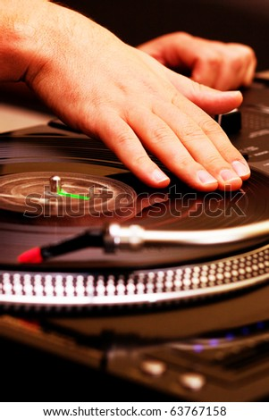 Hands of a DJ scratching analog vinyl record on turntable.Example of hip hop disc jockey doing his routine. Party,concert,educational poster.Audio equipment for professional DJ, music lover enthusiast