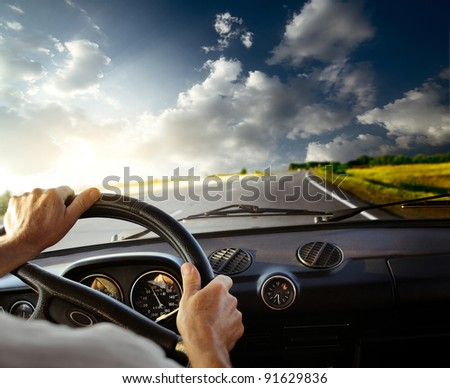 Hands of a driver on steering wheel of a car and empty asphalt road