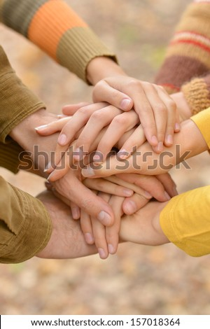 Hands of a family together closeup on autumn background