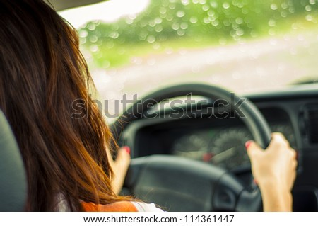 Hands of a female driver on steering wheel