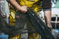 Hands of a fisherman putting away his fishing nets