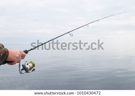 Hands of a fisherman with a spinning rod with the line with a line on a motor boat in the lake on a cloudy day #1010430472