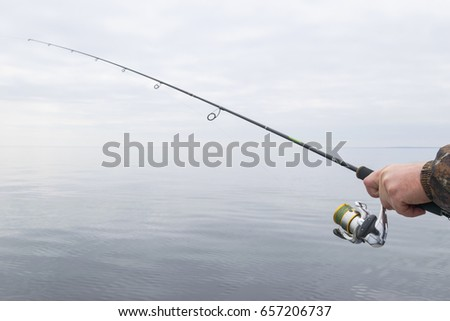 Hands of a fisherman with a spinning rod with the line with a line on a motor boat in the lake on a cloudy day #657206737