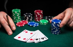 Hands of a gambler closeup and chips on green table in a poker club. A player places a bet on winning poker four of a kind or quads