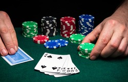 Hands of a gambler closeup and chips on green table in a poker club. A player places a bet on a winning poker flush