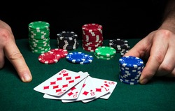 Hands of a gambler closeup and chips on green table in a poker club. A player places a bet on a winning poker straight flush