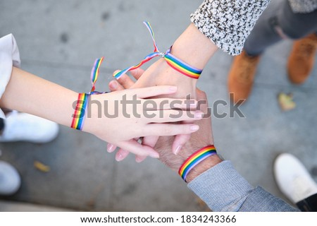 Hands of a group of three people with LGBT flag bracelets. LGBT pride celebration. Stockfoto ©