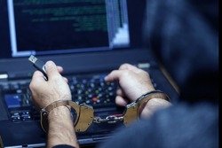 Hands of a hacker in handcuffs holding USB. Prisoner or arrested terrorist in handcuffs, selective focus. Back view.