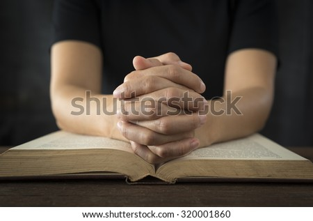 Hands of a human in prayer on a Holy Bible . religion concept. #320001860