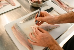 hands of a man chef accurate cleans fresh fish fillets from bones using tweezers. Close-up