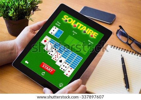 hands of a man gaming solitaire app on tablet over a wooden table. All screen graphics are made up.