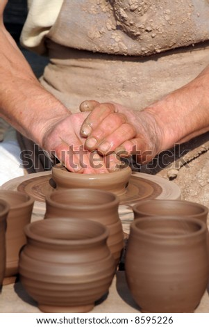 Hands of a man making cups