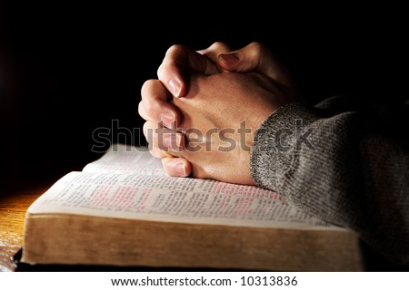 Hands of a man praying in solitude with his Bible (Christian image, shallow focus). - stock photo