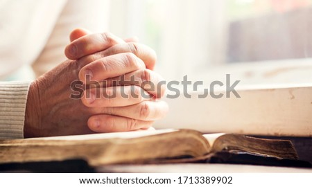 Hands of a man praying over a Bible - represents faith and spirituality in everyday life Foto stock ©