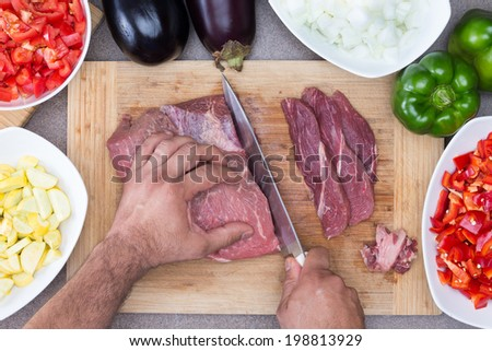 Hands of a man preparing meat and vegetables in a kitchen slicing lean meat on a wooden board with diced zucchini, tomato and onion and whole eggplant and green bell pepper