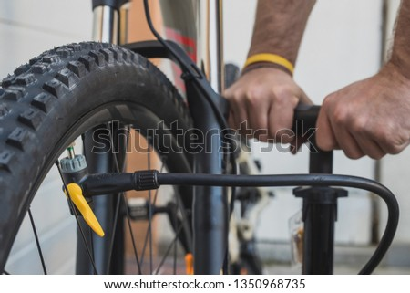 Hands of a man seen pumping a bicycle tire using a stand alone hand pump. MTB tyre being pumped up outside of the house on an overcast day.