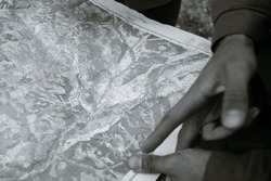 hands of a man showing a location on a geographic map, in black and white