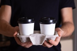 hands of a man who offers to take coffee in paper cups