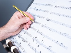 hands of a man writing a musical score or musical sheet, flute or recorder shown, musical composition concept