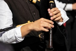 Hands of a musician playing a bagpipe in a festive parade. Galicia, Spain