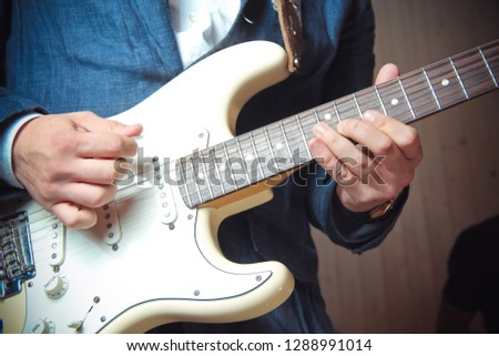 hands of a musician playing electric guitar