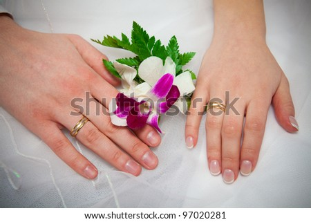 Hands of a newly-married couple, wedding rings and flowers.