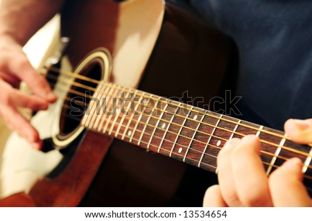Hands of a person playing an acoustic guitar