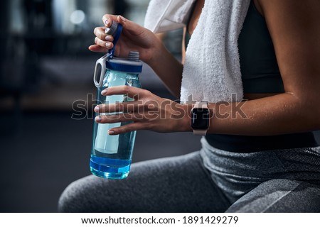 Hands of a person touching an attached bottle cap and shutting the water container with it ストックフォト ©