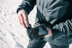 Hands of a photographer inserting the battery into his professional camera in the snow.