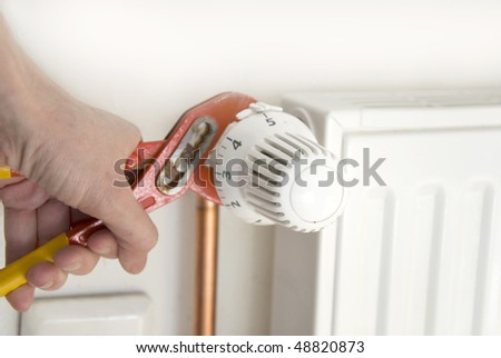 hands of a plumber fixing a radiator