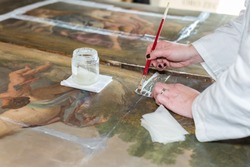 Hands of a Restorer with a Brush: Working on the Restoration of a Painting.