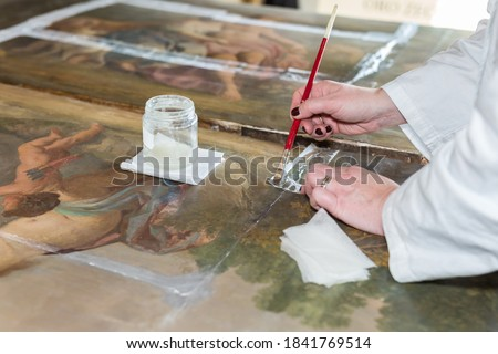Hands of a Restorer with a Brush: Working on the Restoration of a Painting. Сток-фото ©